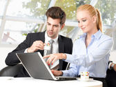 Businessman drinking coffee with his colleague — Stock Photo