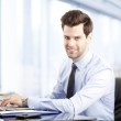 Young businessman using laptop — Stock Photo