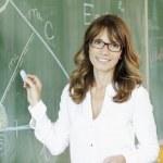 Smiling teacher at blackboard — Stock Photo