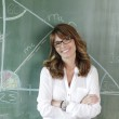 Smiling teacher at blackboard — Stock Photo #33421317