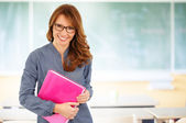 Smiling teacher at blackboard — Stock Photo