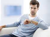 Young man sitting on couch — Stock Photo