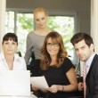 Foto Stock: Positive businesswomsitting with her team