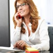Smiling businesswoman on the phone in office — Stock Photo