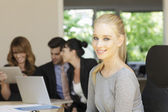 Positive businesswoman sitting with her team — Stock Photo