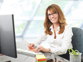 Smiling businesswoman at office desk with a computer — Foto de Stock