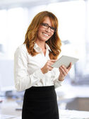 Smiling businesswoman with tablet in office — Stock Photo