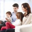 Stock Photo: Happy family sitting in living room