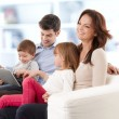Happy family sitting in living room — Stock Photo #39339385