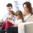 Happy family sitting in living room — Stock Photo #39339433