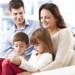 Happy family sitting in living room — Stock Photo #39339551