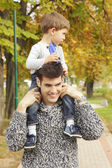 Cute little boy riding piggyback with his dad — Stock Photo
