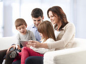 Happy family sitting in living room — Stockfoto