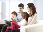 Happy family sitting in living room — Stock Photo