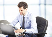 Happy young businessman using laptop in his office — Stock Photo