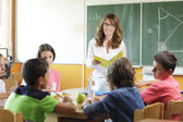 Elementary classroom setting. Focus on teacher and chalkboard. — Stock Photo