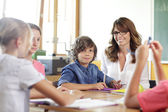 Elementary classroom setting. Focus on school boy. — Stockfoto