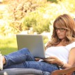 A mature woman working at home in the garden on her laptop. — Stock Photo