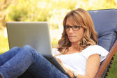 A mature woman working at home in the garden on her laptop. — Foto Stock