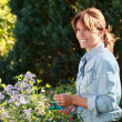Stock Photo: Mature woman taking care of flowers