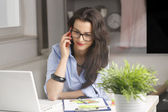 Businesswoman making phone call and working at home — Stock Photo