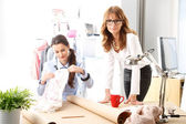 Beautiful fashion designers working together in studio. — Stock Photo