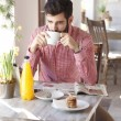 Stock Photo: Young man sitting in coffee shop.