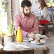 Stock Photo: Modern young man sitting in coffee shop