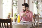 Junger mann sitzt im coffee shop. — Stockfoto
