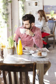 Modern young man sitting in coffee shop — Stock Photo