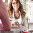 Beautiful woman at desk in coffee shop — Stock Photo #41396439