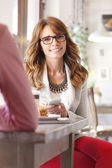 Beautiful woman at desk in coffee shop — Stock Photo