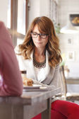 Beautiful woman sitting in coffee shop — Stock Photo