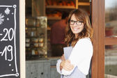Woman standing in front of coffee shop — Stockfoto