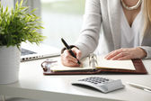 Businesswoman makes a note in notebook. — Stock Photo