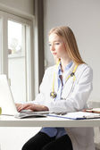 Female doctor smiling and working — Stock Photo