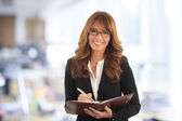 Professional businesswoman standing in office — Stock Photo