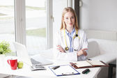 Young female doctor sitting at desk in clinic. — Stock Photo