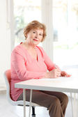 Senior woman sitting at desk — Stock Photo