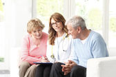 Elderly couple consulting with doctor — Stock Photo