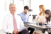 Senior businessman smiling at meeting — Stock Photo