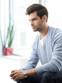 Modern young man relaxing on sofa — Stock Photo