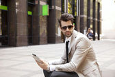 Modern businessman in front of business center — Stock Photo