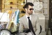 Modern businessman sitting on scooter — Stock Photo