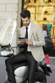 Businessman with tablet on scooter — Stock Photo