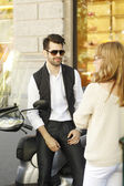 Businessman with scooter discussing with woman — Stock Photo