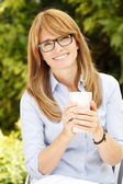 Lady with mug in garden — Stock Photo