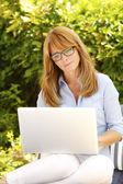 Beautiful mature woman with laptop — Fotografia Stock