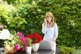 Flower shop owner using mobile phone — Stock Photo