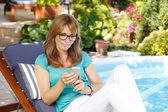 Woman in garden using mobile — Stock Photo